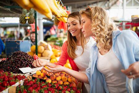 Jonge gelukkige vrouwen die groenten en fruit op de markt winkelen Stockfoto