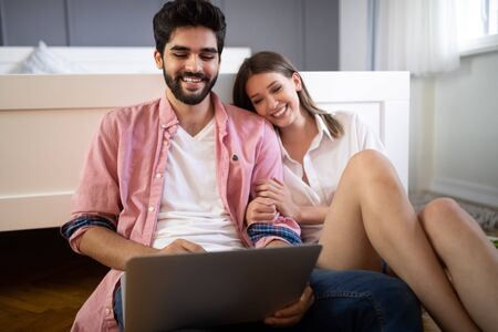 Happy smiling couple using laptop at home Фото со стока