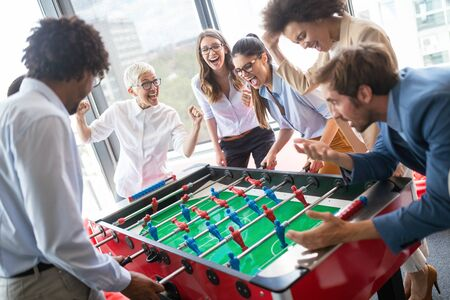 Multiracial people having fun in office room, excited diverse employees enjoying activity at work Stock Photo