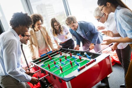 Business people having great time together.Colleagues playing table football in modern office Stock Photo