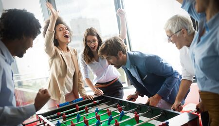 Excited diverse employees enjoying funny activity at work break, creative friendly workers play game Stock Photo