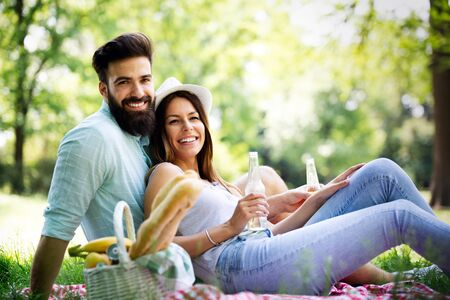 Happy young couple enjoying picnic in park. Stock Photo
