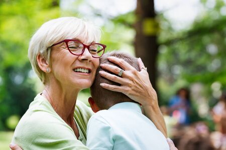 Loving senior woman embracing her grandchildren with a cheerful smile on her face