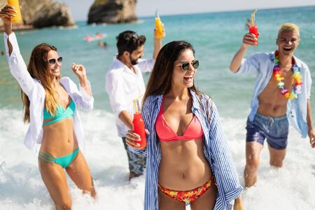 Group of young happy friends on vacation having fun on beach in summer