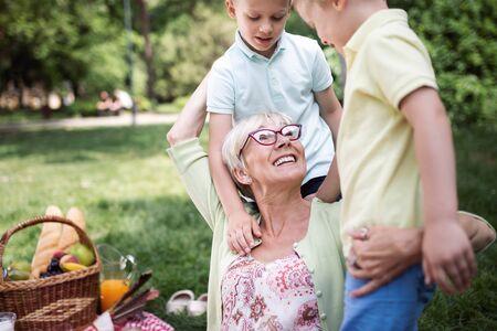 Amorosa mujer mayor abrazando a sus nietos con una alegre sonrisa en su rostro