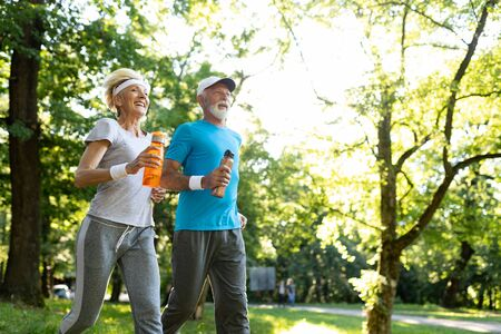 Mature couple jogging and running outdoors in nature Stockfoto