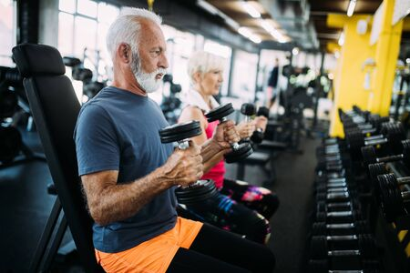 Happy fit mature man in gym working out to stay healthy Stok Fotoğraf