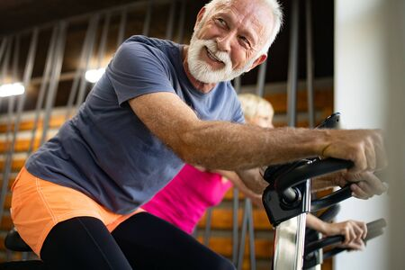 Mature fit people biking in the gym, exercising legs doing cardio workout cycling bikes Reklamní fotografie