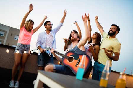 Young friends having fun at a rooftop party, playing the guitar, singing, dancing and drinking