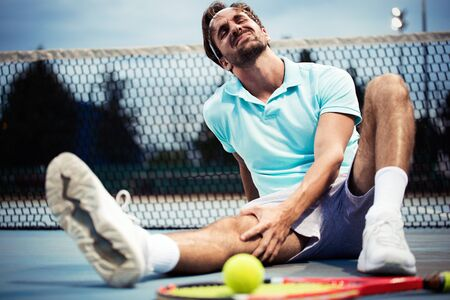 Sports injury. Young tennis player touching his knee while sitting on the tennis court Stock Photo