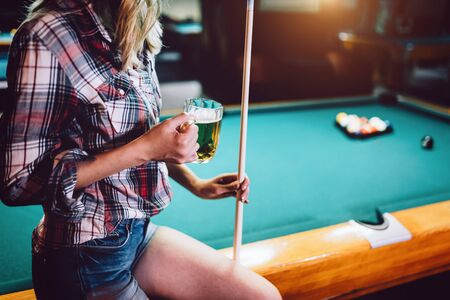 Young beautiful girl is playing billiards. Pleasant pastime, rest, entertainment. Archivio Fotografico - 127062635