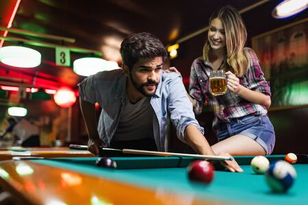 Young couple playing snooker together in bar Archivio Fotografico - 127062640