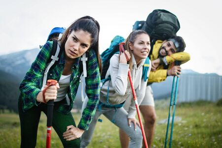 Gorup of friends climbing up hill, with backpacks and climbing stick Stock fotó - 127065022