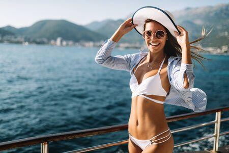 Beach vacation. Beautiful woman in sunhat and bikini enjoying summer trip