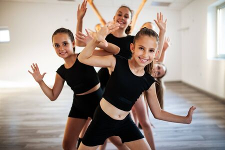 Group of fit happy children exercising ballet in studio together Imagens