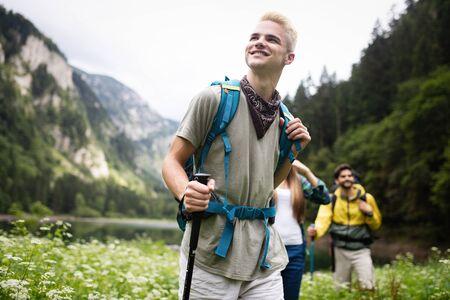 Grupa szczęśliwych przyjaciół z plecakami wędrujących razem