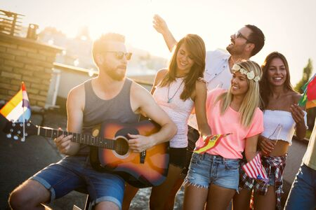 Groupe d'amis heureux ayant la fête sur le toit