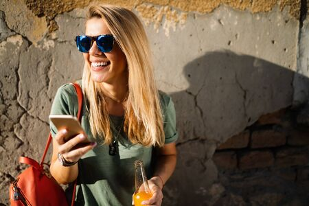 City lifestyle, hipster girl using a phone texting on smartphone app in a street