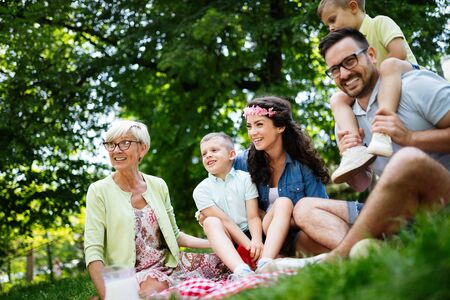 Multi generation family enjoying picnic in a park 写真素材 - 128584712