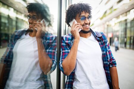 Young black man smiling and talking on mobile phone outside Banco de Imagens