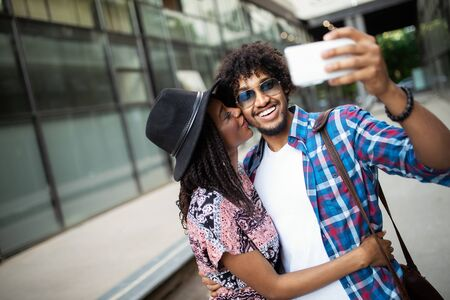 Young african couple pose for holiday selfie in city