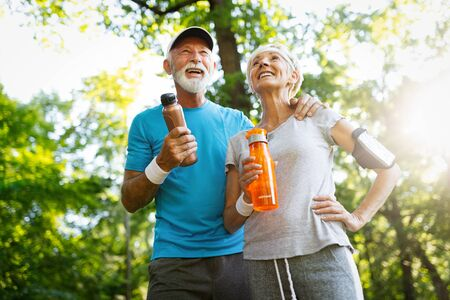 Senior couple staying hydrated after running jogging