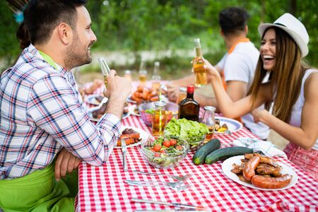 Friends making barbecue and having lunch in the nature Stockfoto - 128584815