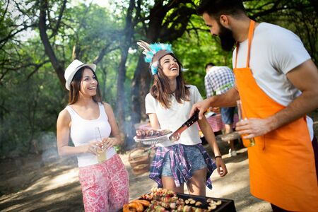 Friends making barbecue and having lunch in the nature Stockfoto - 128584825