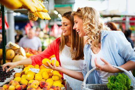 Jóvenes mujeres felices comprando frutas y verduras en el mercado