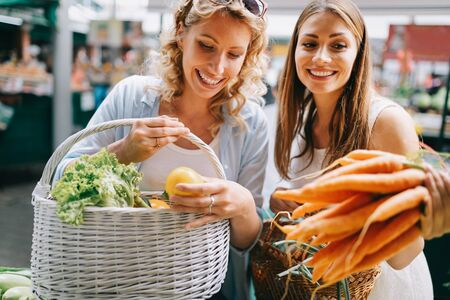 Beautiful happy women shopping vegetables and fruits Imagens