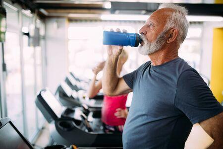 Senior man drinking bottle of water on threadmill in gym