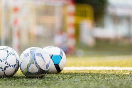 Picture of three soccer balls on field Фото со стока