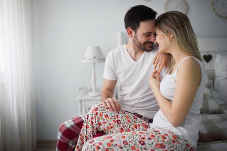 Picture of young attractive couple kissing on bed