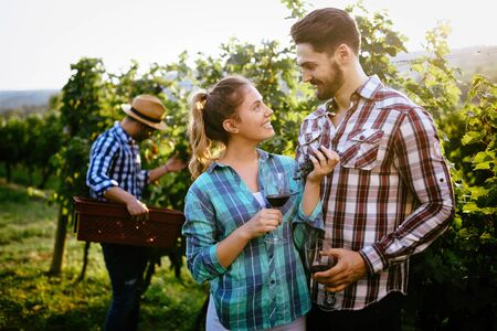 Winemaker family together tasting vine in vineyard