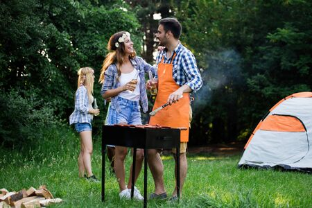 Happy group of friends making a barbecue together outdoors in the nature Фото со стока