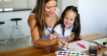 Mother looking how her child daughter drawing Stock Photo - 128970645