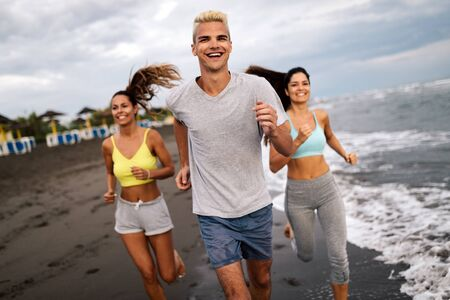 Group of people, friends running on the beach at sunset