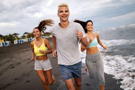 Grupo de personas, amigos corriendo en la playa al atardecer