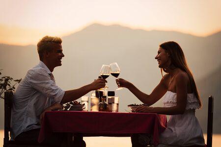 Concepto de personas, vacaciones, amor y romance. Pareja joven disfrutando de una cena romántica en la playa.