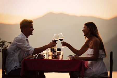 People, vacation, love and romance concept. Young couple enjoying a romantic dinner on beach. Foto de archivo - 128972890