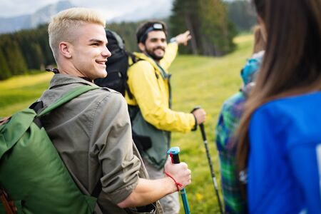 Adventure, travel, tourism, hike and people concept - group of smiling friends with backpacks and map outdoors Zdjęcie Seryjne