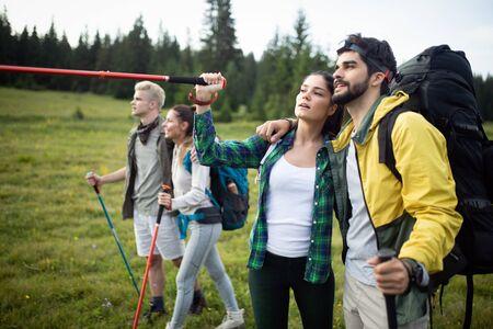 Group of friends on a mountain. Men and women climbing rocks.