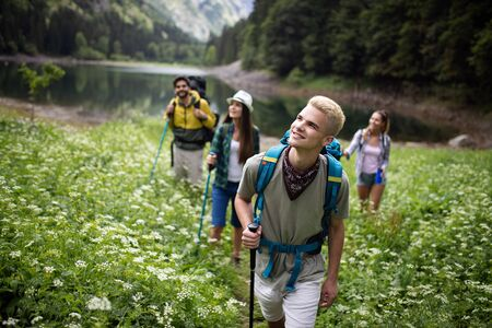 Smiling friends walking with backpacks. Adventure, travel, tourism, hike and people concept. Zdjęcie Seryjne - 128904444