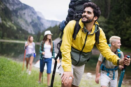 Group of smiling friends hiking with backpacks outdoors. Travel, tourism, hike and people concept. Zdjęcie Seryjne