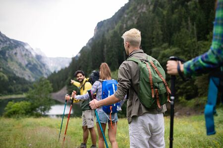 Smiling friends walking with backpacks. Adventure, travel, tourism, hike and people concept. Zdjęcie Seryjne - 128904453