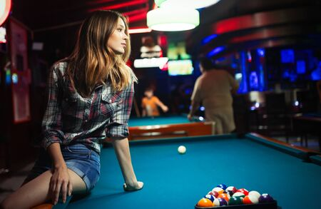 Young beautiful girl is playing billiards. Pleasant pastime, rest, entertainment. Archivio Fotografico - 129270163