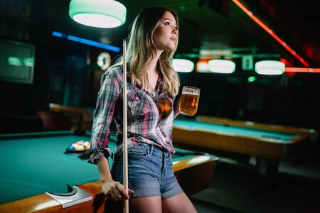Young beautiful girl is playing billiards. Pleasant pastime, rest, entertainment. Archivio Fotografico - 129270169