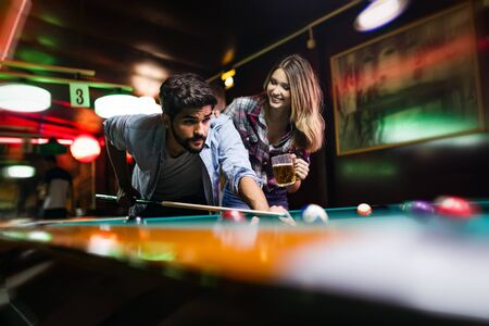 Couple dating, flirting and playing billiard in a pub Archivio Fotografico - 129270317