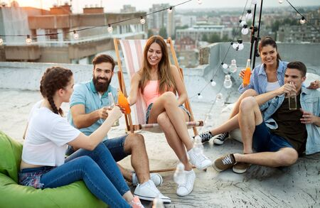 Friends having party on top of the roof. Fun, summer, city lifestyle and friendship concept Banco de Imagens