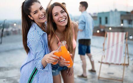 Beautiful women friends on the balcony having fun at party. Banco de Imagens